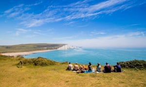 Walkers sitting at the cliff edge looking towards Cuckmere Haven, Seven Sisters country park near Eastbourne, East Sussex, UK