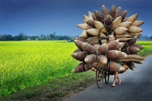 Man transporting bamboo fishing baskets, Tat Vien village, Hung Yen Province, Vietnam