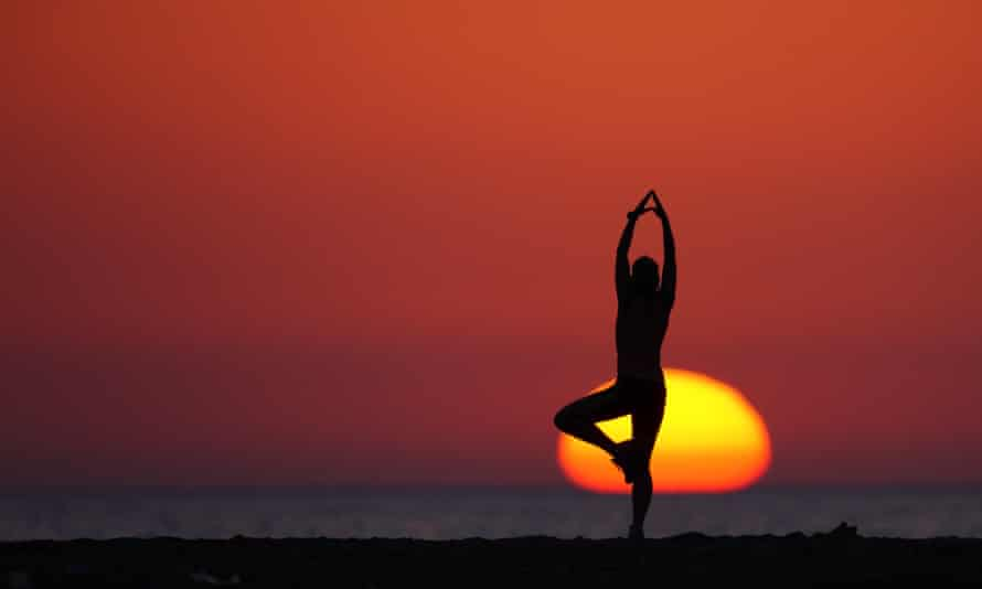 A woman exercising on the beach at sunset in Rhodes, Greece