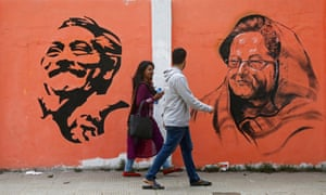 Dhaka residents stroll past a mural of Bangladesh's assassinated founder, Sheikh Mujibur Rahman, and his daughter, Sheikh Hasina, the current prime minister.