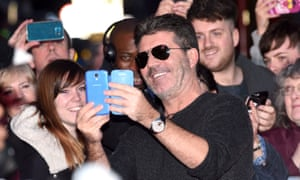 Simon Cowell takes a picture with fans at auditions for Britain's Got Talent in Birmingham.