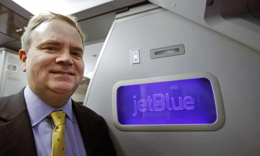 Robin Hayes, JetBlue's chief executive on a plane with JetBlue's logo behind him