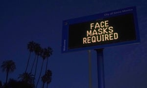 A sign reminding people to wear a mask stands along the Pacific Coast Highway in Santa Monica.