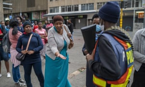 A woman waiting for a taxi pleads with a police officer to let taxi operators drive in Johannesburg on 29 March. Some drivers were missing a permit to operate during South Africa's lockdown.