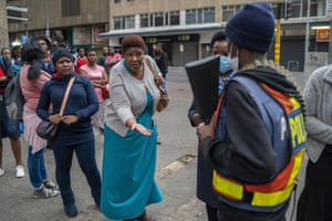 A woman waiting for a minibus taxi pleads with police to let taxi drivers operate during the coronavirus lockdown.