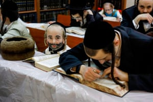Ultra-Orthodox Jews including a child in costume study during the feast of Purim at a synagogue in the Israeli city of Bnei Brak