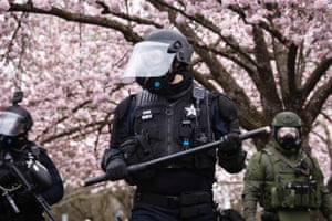 Salem, US. A police officer in riot gear holds a baton after an official declaration of an unlawful assembly during an anti-fascist rally in Oregon