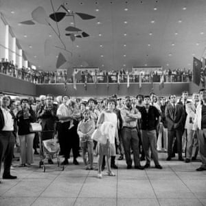 A crowd of passengers at the International Arrival Building at John F. Kennedy International Airport, NYC, standing under a massive mobile (titled .125 and designed by artist Alexander Calder), watch a large screen television showing the Apollo 11 moon landing mission