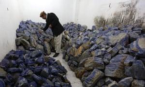 An Afghan businessman checks lapis lazuli at his shop in Kabul.