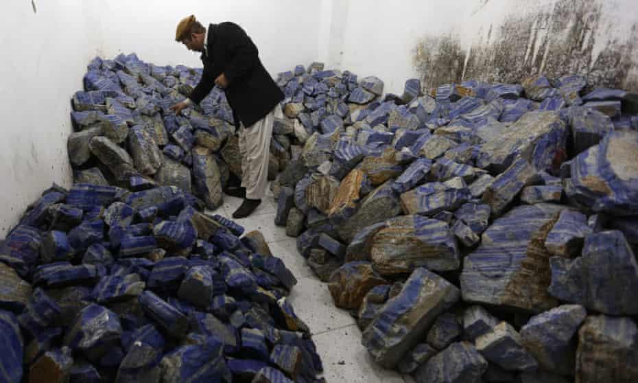An Afghan man checks lapis lazuli at his shop in Kabul.