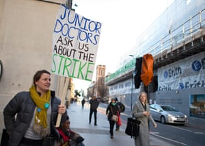 A junior doctor holds a banner inviting the public to ask about the strike, outside Guy's hospital in London