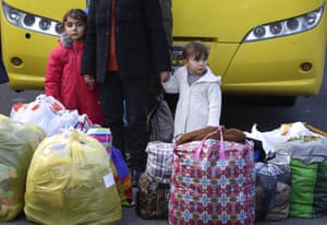 Ethnic Armenian refugees stand with their bags as they return to Stepanakert, the capital of the separatist region of Nagorno-Karabakh.