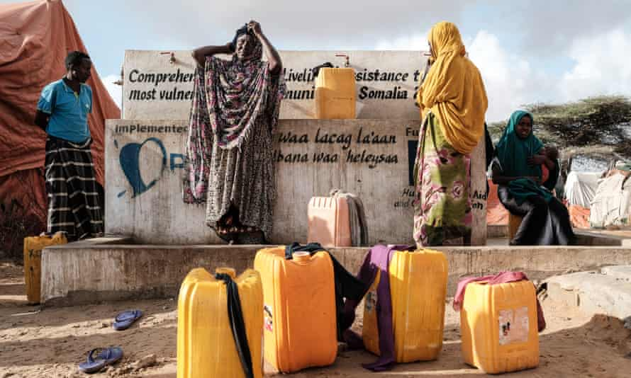 Displaced Somali women fill jerrycans at a water point in Mogadishu