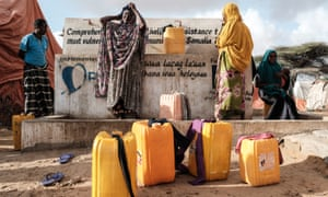Women fill jerrycans with water from a well. In Somalia, where cholera outbreaks have killed hundreds of people, the looming famine threatens 6.2 million people, more than half the population