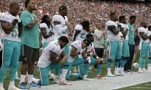 Arian Foster, Kenny Stills and Michael Thomas kneel during the national anthem on Sunday