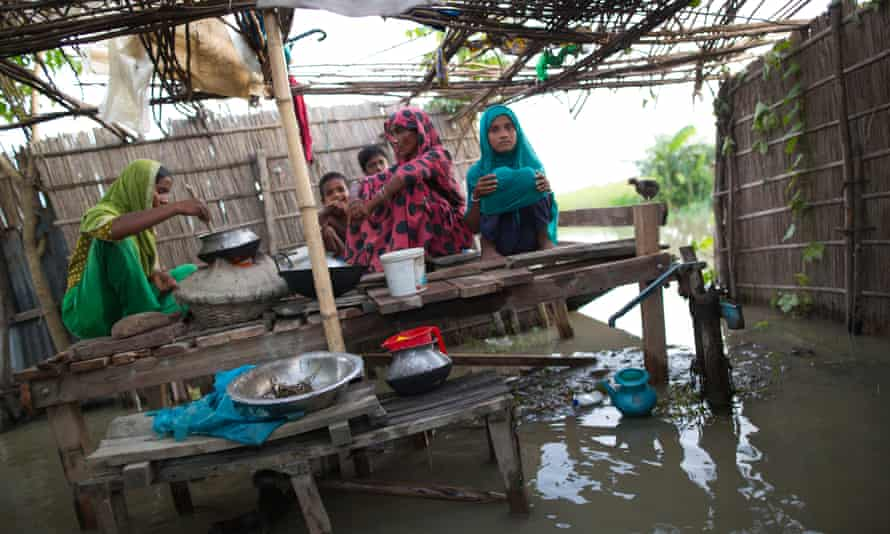 A family cooks food on a cot in flood-hit Lalmonirhat, Bangladesh – a country among the most vulnerable to the consequences of climate change.