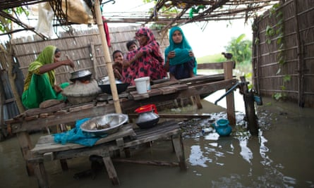 A family cooking amid floodwater in Lalmonirhat, Bangladesh, 2017.