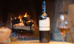 Glass of wine and bottle by fireplace