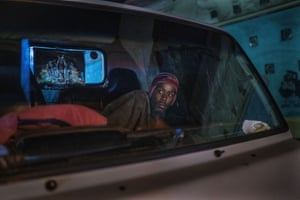 A man living in his car reacts to police and army patrolling central Johannesburg during the Covid-19 lockdown.