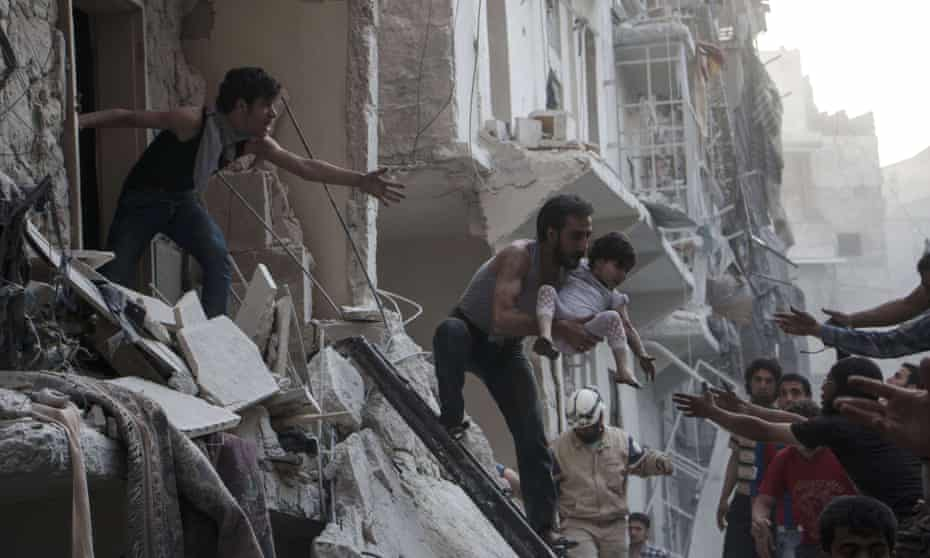 A man carries a child from a building following a reported barrel bomb attack