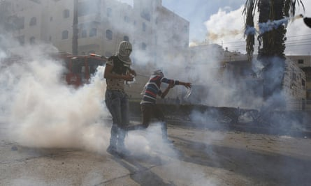 A Palestinian protester hurls back a teargas canister fired by Israeli troops during clashes in the West Bank city of Hebron.