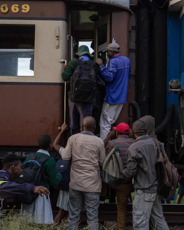 Commuters jostle to board the train