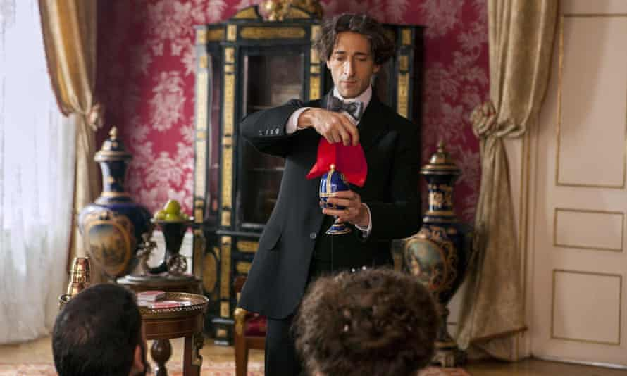 Adrien Brody holding a red handkerchief over a vase, conducting a trick