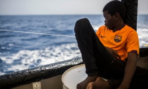Khingsley Dokowada, nine, from Central African Republic, rests on the deck of a Spanish NGO vessel.