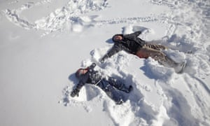 Brian McAlear and his son Christian, 4, make snow angels in the memorial park in Leonia, New Jersey