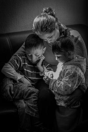 Mexico City, Mexico, 2019. Greta Rico Siomara cradles her niece and nephew at their home in Mexico