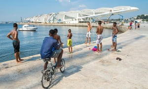 Young people contemplate leaping into the sea by the Museum of Tomorrow