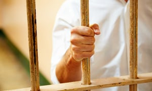 Man holding bars of jail cell.