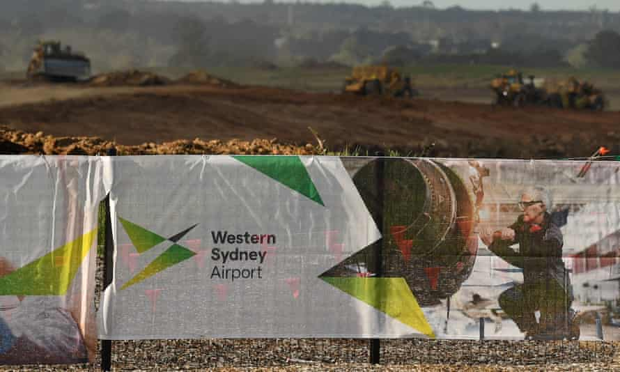 sign in front of tractors working land that says western sydney airport