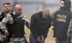 Adélio Bispo de Oliveira, suspected of stabbing Bolsonaro, is escorted by police at the airport in Juiz de Fora on 8 September.