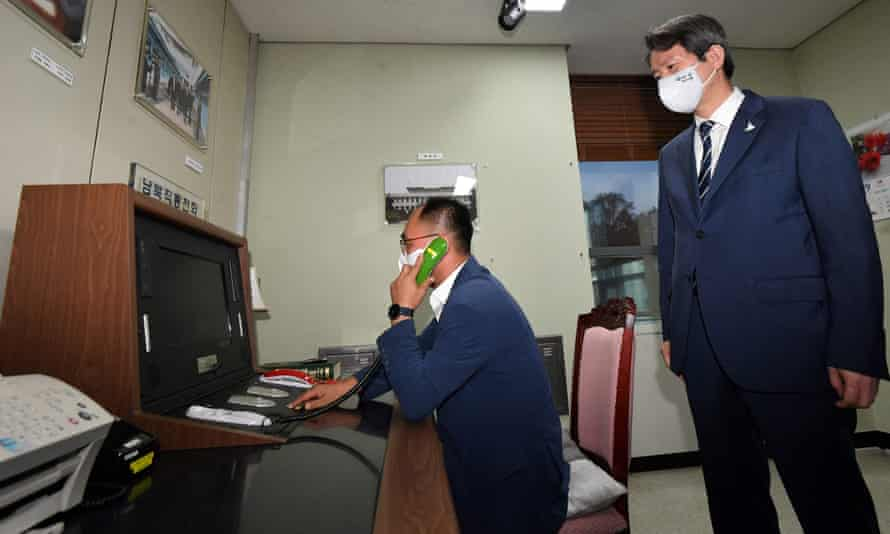 """This file photo taken on September 16, 2020 shows South Korea's Unification Minister Lee In-young (R) looking at the inter-Korean """"hotline"""" during a visit to the south side of the truce village of Panmunjom"""