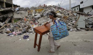 A woman carries a table through the street after an earthquake in Pedernales