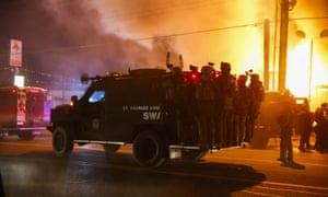 Police ride on a vehicle past a burning building that was set ablaze by protestors in Ferguson
