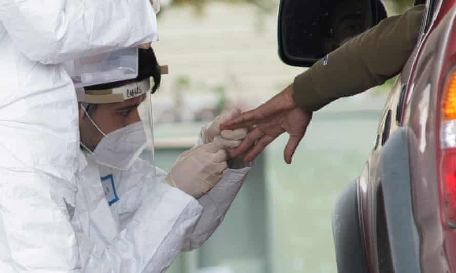 A medical professional conducts tests for coronavirus in Bolinas, a coastal enclave in northern California, on Monday.