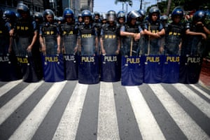Manila, Philippines: Police officers in riot gear stand in formation as protesters attempt to march to the US embassy