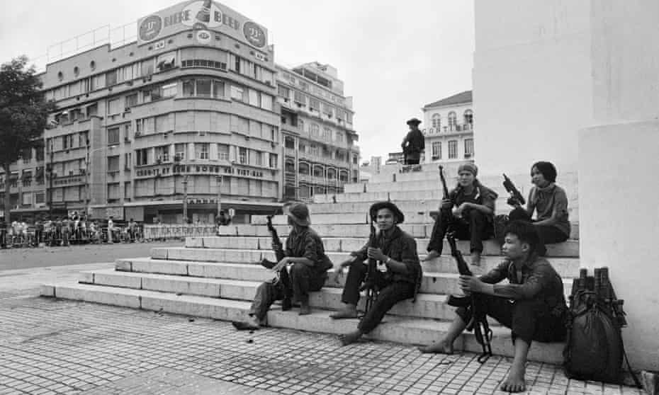 Group of North Vietnamese soldiers with their weapons sitting on steps smoking in a square in central Saigon