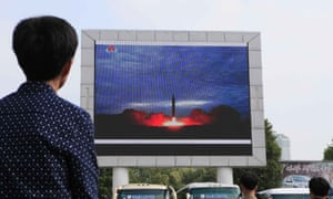 People watch a televised news broadcast of the test-fire of an intercontinental ballistic rocket, 30 August, in Pyongyang, North Korea.
