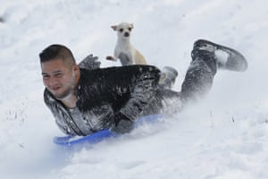 Kansas City, USJonny Mendoza and his dog Subi sled down a snowy hill in a park. A winter storm brought blizzard-like conditions dumping about 6 inches of snow on the the Kansas City area Sunday before moving east Monday, grounding hundreds of flights and causing some road traffic chaos