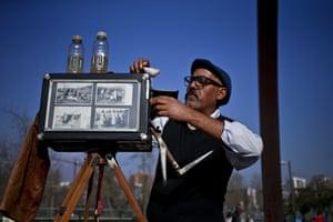 Luis Maldonado prepares his old wooden box camera at a fair in Santiago, Chile. Maldonado is the last remaining photographer in the main square of the Chilean capital still using a wooden box camera
