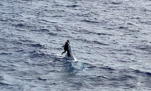 Atlantic Ocean Stuart Bee, who went missing on Friday, clings to the hull of his 32ft capsized vessel, approximately 86 miles east of Cape Canaveral in Florida, before being rescued by the crew aboard the US coast guard container ship Angeles