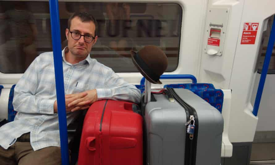 Man on tube with bags, London.