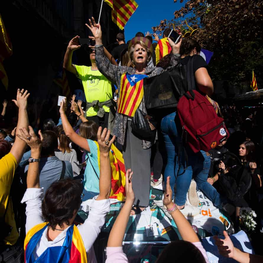 People demonstrate on a Spanish Guardia Civil car as officers search the Catalan vice-president's office in Barcelona