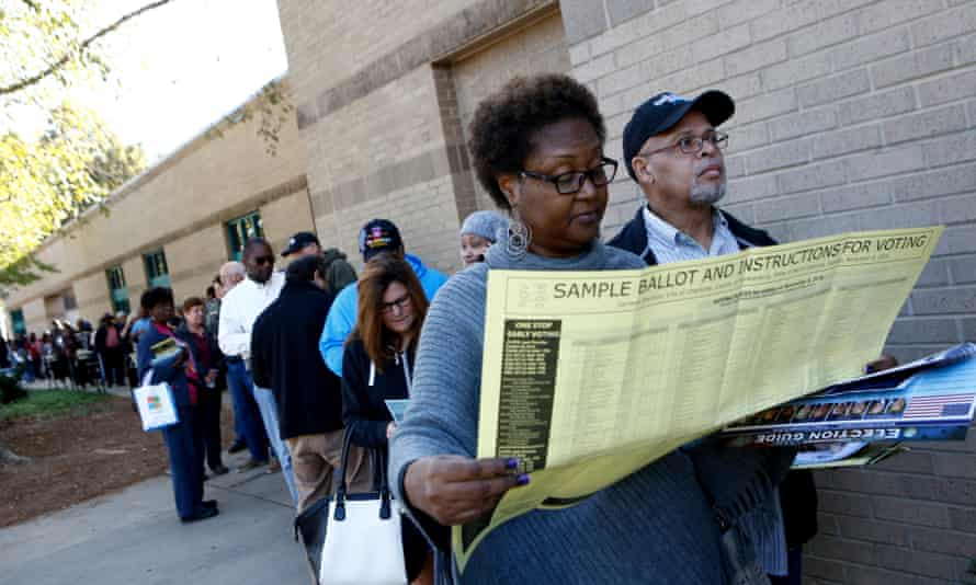 Mavis Wilson looks over a sample ballot as she waits to vote early with her husband, Ron, in Charlotte, North Carolina.