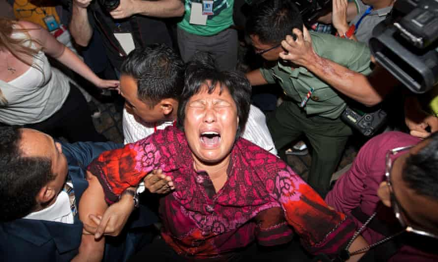 A family member of someone missing on Malaysia Airlines flight MH370 breaks down in March 2014