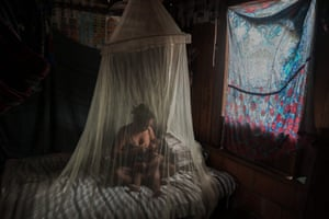 Priscila Tavares Batista breastfeeds her son Jone  in a bed protected by a mosquito net, after being treated with medicinal herbs having shown symptoms of Covid-19, in the Wakiru community.