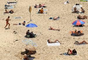 Beachgoers social distance on the sand at Bondi